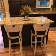 Two white wood counter stools